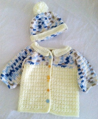 A unisex, crocheted sweater and hat set, featuring moon and star buttons. (Size 3-9 months)
