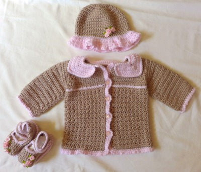 A crocheted brown and pink set including a hat, booties, and a cardigan. (Size 3-9 months.)