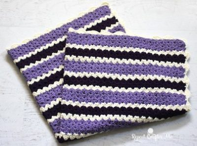 Cluster V-Stitch Striped Blanket with Shell Border, free crochet pattern by Repeat Crafter Me | 12 free crochet patterns for baby blankets, roundup curated by Crochet Pattern Bonanza for Underground Crafter. Crocheted baby blankets are perfect for keeping your little ones super cozy in the cold winter weather. They are not only great for the crib, but they also make for excellent covers in the stroller, or in the car. And to make them super cozy, you can always line them with a cotton or fleece material.