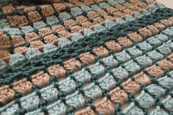 Beach Stroll Memories Shawl, free crochet pattern in Cloudborn Superwash Merino Worsted Twist yarn by Underground Crafter | I love the soothing, repetitive motions of making granny squares. This rectangular shawl uses a variation on the traditional granny square pattern. It's easy to adapt the pattern to your favorite size. The stitch pattern allows for a bit of air flow so you don't get too hot when wearing it.