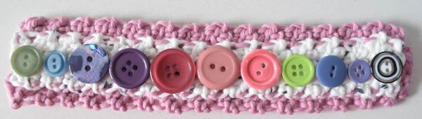 Free crochet pattern: Layered Button Cuff in Wool and the Gang Shiny Happy Cotton by Underground Crafter | After 10 years, I finally organized my grandmother's button collection using a Deflecto Stackable Caddy Organizer. With buttons now at the ready, I used a soft cotton yarn to make a fun accessory. Make it your own by changing up yarn colors or using different styles of buttons.