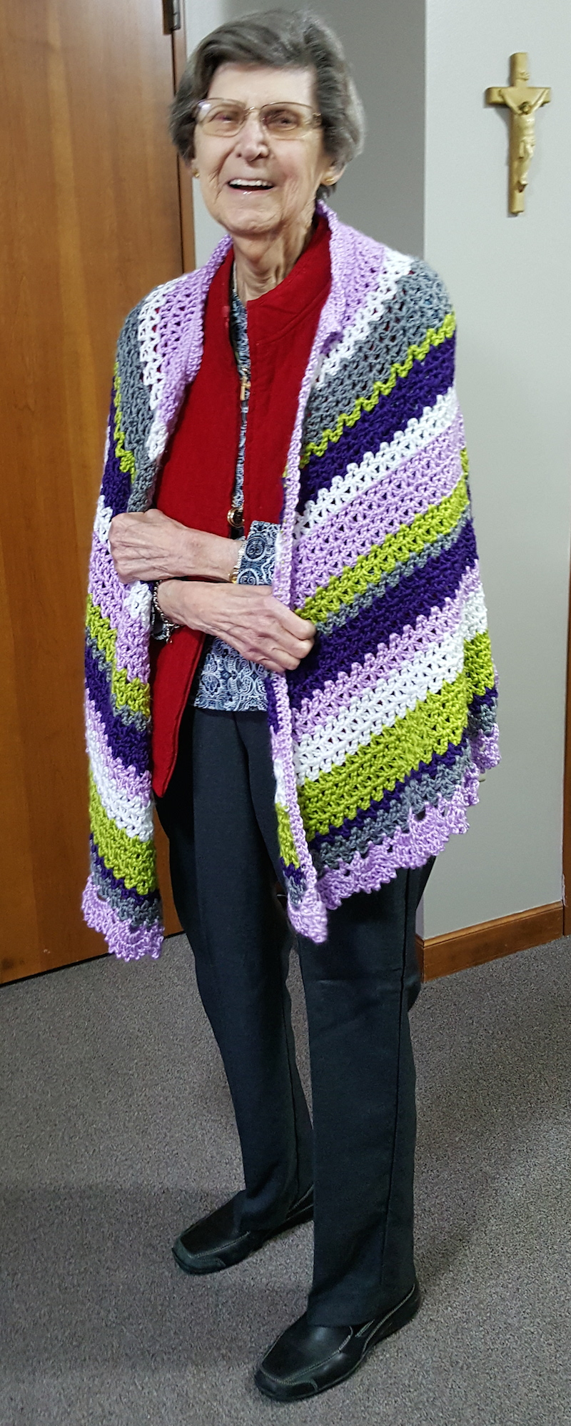 Woman wearing multi-color crochet shawl standing in hallway | Free crochet pattern: Aunt Gladys Shawl by J Crochet for Underground Crafter
