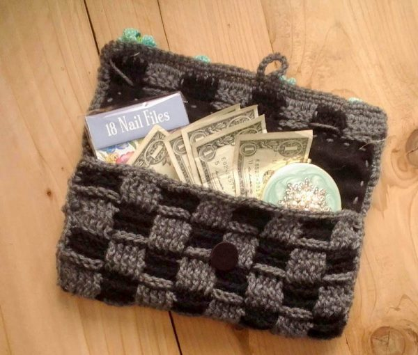 Black and gray crochet clutch open with money and other items inside | Free crochet pattern: Basket of Posies Clutch by BellaTu Boheme for Underground Crafter