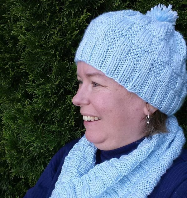 Smiling woman wearing blue knit hat and cowl set | Carmen Nuland/A Simple Homestead