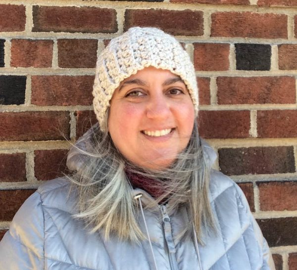 Woman in lacy crochet hat in chunky yarn smiling and wearing silver coat | Free crochet pattern: Chunky Double V-Stitch Hat in Sprightly Acrylic Super Bulky yarn by Underground Crafter
