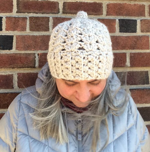 Woman in lacy crochet hat in chunky yarn facing down | Free crochet pattern: Chunky Double V-Stitch Hat in Sprightly Acrylic Super Bulky yarn by Underground Crafter