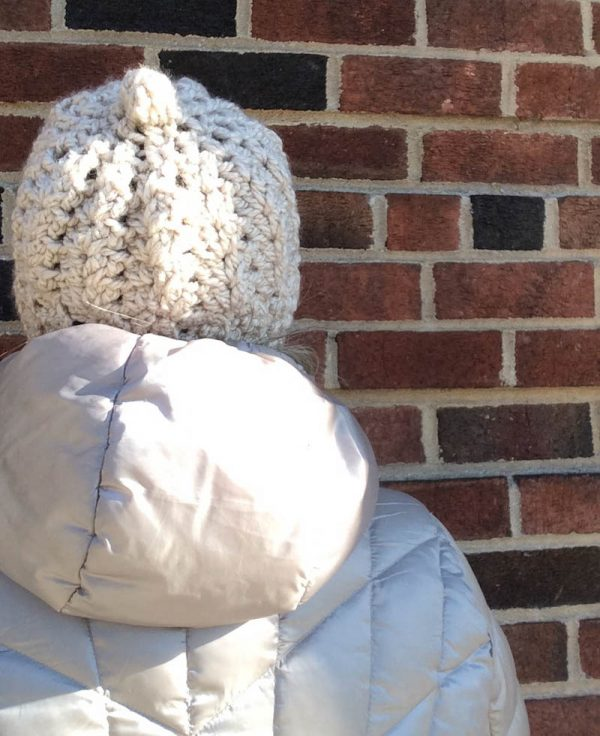 Back of woman with silver coat and crochet hat in chunky yarn | Free crochet pattern: Chunky Double V-Stitch Hat in Sprightly Acrylic Super Bulky yarn by Underground Crafter