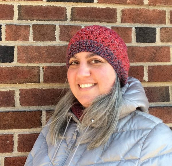 Smiling woman wearing striped crochet hat and silver coat against a brick wall | Free crochet pattern: Flattened Shell Hat in 4 sizes in Cascade 220 Superwash Wave yarn by Underground Crafter