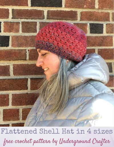 Smiling woman looking down while wearing striped crochet hat and silver coat against a brick wall | Free crochet pattern: Flattened Shell Hat in 4 sizes in Cascade 220 Superwash Wave yarn by Underground Crafter