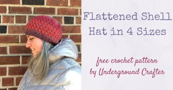 Woman looking down while wearing striped crochet hat and silver coat against a brick wall | Free crochet pattern: Flattened Shell Hat in 4 sizes in Cascade 220 Superwash Wave yarn by Underground Crafter
