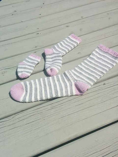 Striped crochet socks laid flat on wooden surface | Free crochet pattern: Ice Cream Socks, Part 1 by ACCROchet (with tips for first-time sock crocheters) on Underground Crafter