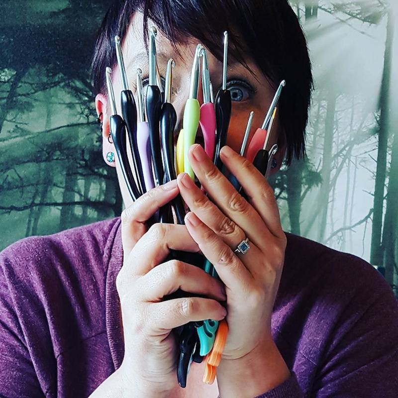 Woman holding many crochet hooks in front of her face | Free crochet pattern: Ice Cream Socks, Part 1 by ACCROchet (with tips for first-time sock crocheters) on Underground Crafter