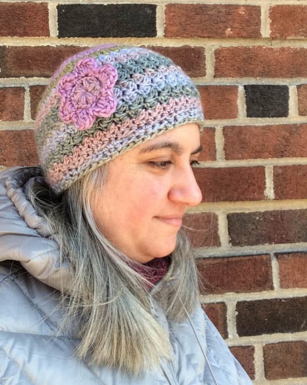 Profile of woman wearing multi-color crochet hat with floral applique, standing against brick wall in a silver coat | Free crochet pattern: New Dawn Beanie in Sprightly Spectrum Worsted yarn by Underground Crafter