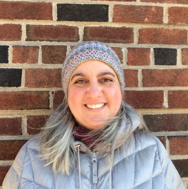 Smiling woman wearing multi-color crochet hat, standing against brick wall in a silver coat | Free crochet pattern: New Dawn Beanie in Sprightly Spectrum Worsted yarn by Underground Crafter