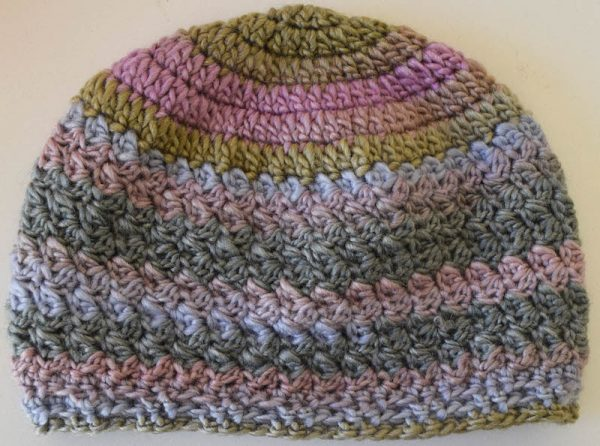 Multi-color crochet hat flat on off-white surface. | Free crochet pattern: New Dawn Beanie in Sprightly Spectrum Worsted yarn by Underground Crafter