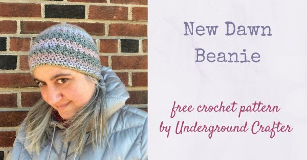 Profile of woman wearing multi-color crochet hat while looking downwards and standing against brick wall in a silver coat. | Free crochet pattern: New Dawn Beanie in Sprightly Spectrum Worsted yarn by Underground Crafter
