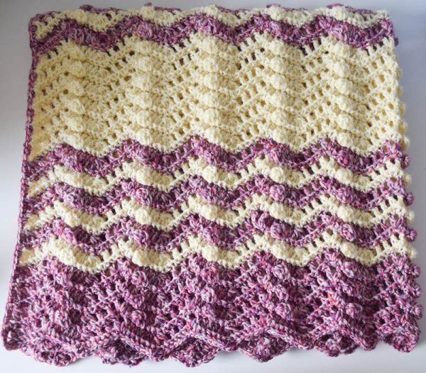 Striped, textured crochet ripple blanket folded and laying flat. | Free crochet pattern: Berry Cobbler Ripple Blanket in Cascade 220 Superwash Effects and 220 Superwash yarns by Underground Crafter