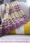 Striped, textured crochet ripple blanket slung over armchair with pillow. | Free crochet pattern: Berry Cobbler Ripple Blanket in Cascade 220 Superwash Effects and 220 Superwash yarns by Underground Crafter