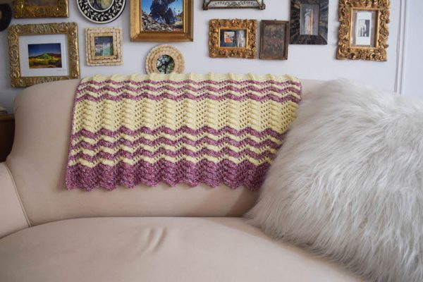 Striped, textured crochet ripple blanket on back of couch with pillow. | Free crochet pattern: Berry Cobbler Ripple Blanket in Cascade 220 Superwash Effects and 220 Superwash yarns by Underground Crafter
