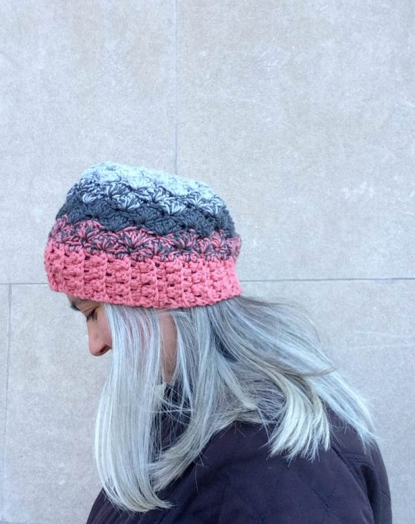 Woman with grey hair and black coat wearing crocheted ombré hat in pink and grays | Free crochet pattern: Ombré Shells Hat in Willow & Lark Ramble by Underground Crafter