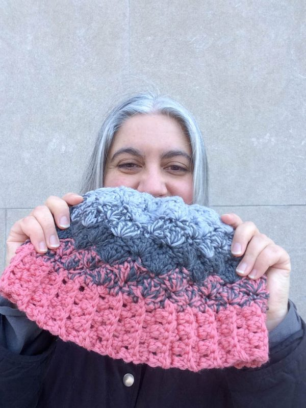 Woman with grey hair holding crocheted ombré hat in pink and grays | Free crochet pattern: Ombré Shells Hat in Willow & Lark Ramble by Underground Crafter