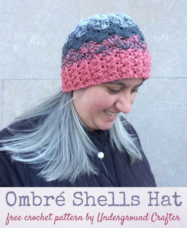 Free crochet pattern: Ombré Shells Hat in Willow & Lark Ramble by Underground CrafterWoman with grey hair and black coat wearing crocheted ombré hat in pink and grays |