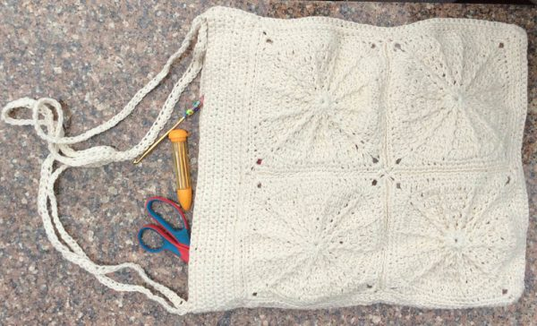 Crochet motif bag made with undyed yarn laying flat on stone surface with scissors and tapesty needles tumbling out of bag. | Free crochet pattern: Clarice Carryall in Appalachian Baby Design Organic Cotton Sport yarn by Underground Crafter