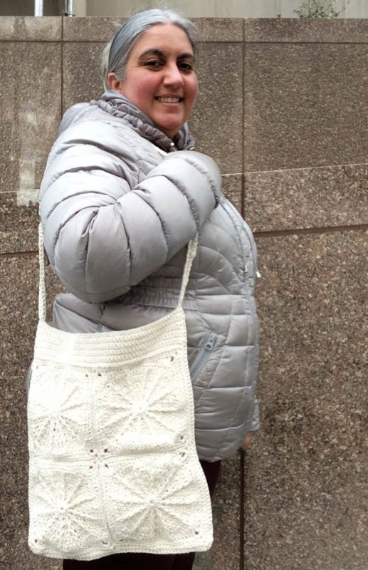 Profile of woman wearing silver coat and maroon pants while carrying crochet motif bag made with undyed yarn. | Free crochet pattern: Clarice Carryall in Appalachian Baby Design Organic Cotton Sport yarn by Underground Crafter