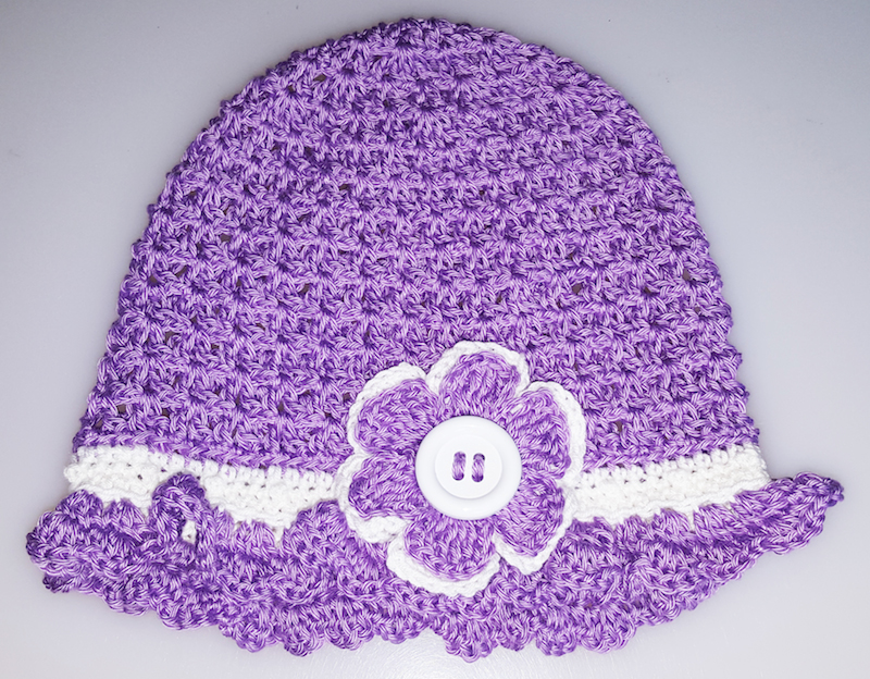 Purple crochet hat with flower laid flat | Free crochet pattern: Emily Hat by J Crochet in Cascade Ultra Pima Fine for Underground Crafter