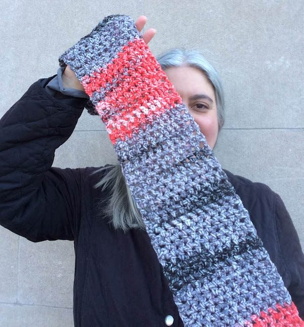 Woman holding colorful crochet scarf in front of face and wearing a black jacket | Free crochet pattern: Tweed Stitch Keyhole Scarf in Cascade Anthem Chords by Underground Crafter