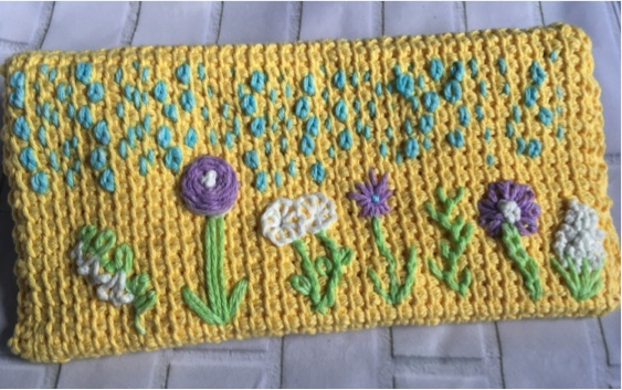 Fiducia Clutch, free Tunisian crochet pattern with embroidery tutorials by Fiat Fiber Arts for Underground Crafter | Back of Tunisian crochet clutch with rain and flowers embroidered on it