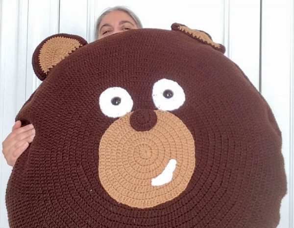 Free crochet pattern: Kodiak Bear Pillow Pal by Underground Crafter - Marie holding pillow pal for scale