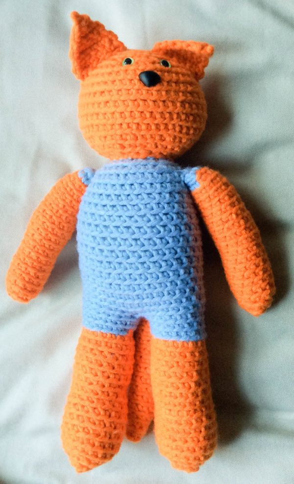 Free crochet pattern: Kitty in a Romper in Paintbox Yarns Wool Mix Chunky yarn stuffed with Fairfield Poly-Fil Royal Silk Fiber Fill by Underground Crafter - cat amigurumi on bed