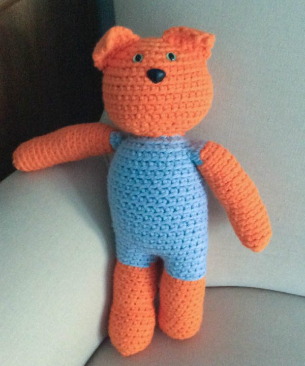 Free crochet pattern: Kitty in a Romper in Paintbox Yarns Wool Mix Chunky yarn stuffed with Fairfield Poly-Fil Royal Silk Fiber Fill by Underground Crafter - cat amigurumi standing at edge of couch