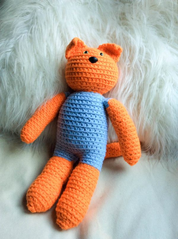 Free crochet pattern: Kitty in a Romper in Paintbox Yarns Wool Mix Chunky yarn stuffed with Fairfield Poly-Fil Royal Silk Fiber Fill by Underground Crafter - cat amigurumi sitting against pillow