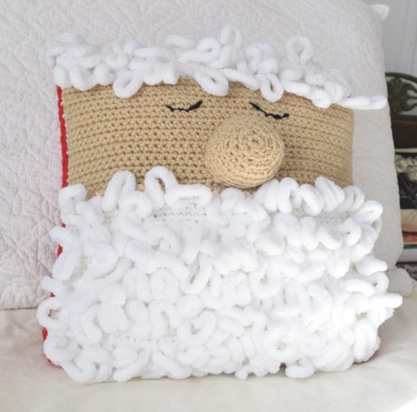 Free crochet pattern: Sleepy Santa Pillow in Red Heart Super Saver and Loop-It yarns with Fairfield World Crafter's Choice Pillow by Underground Crafter | pillow on bed