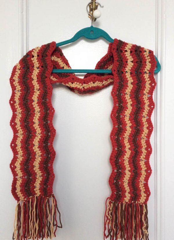 Free crochet pattern: Bonfire Fringe Scarf in Paintbox Yarns Simply Chunky yarn by Underground Crafter | striped crochet ripple scarf with fringe on hanger