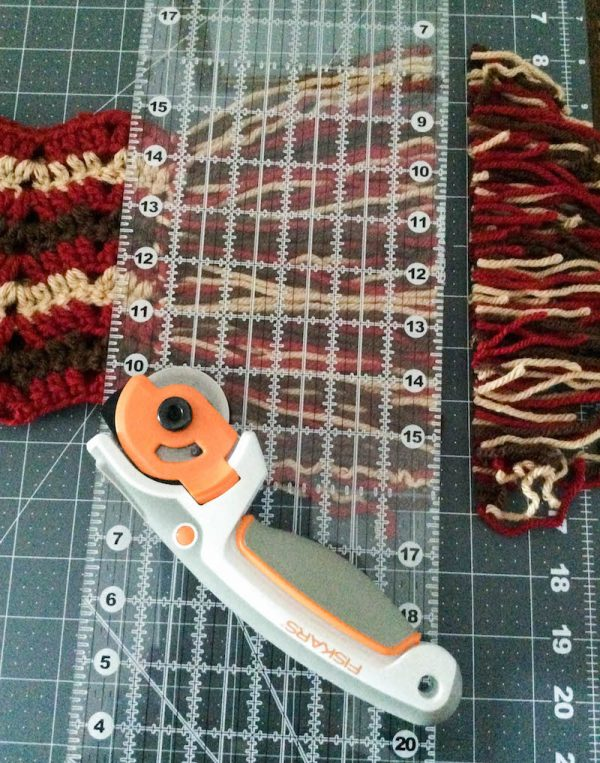 Free crochet pattern: Bonfire Fringe Scarf in Paintbox Yarns Simply Chunky yarn by Underground Crafter | cutting fringe with Fiskars rotary cutter