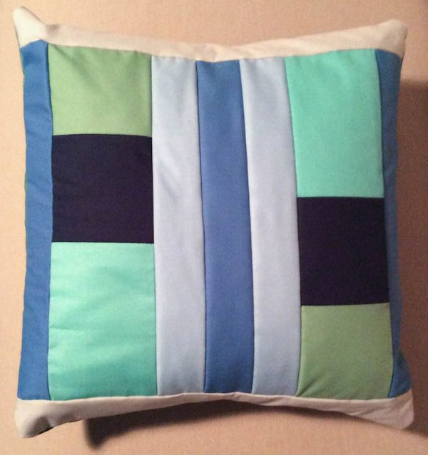 Modern Quilt Pillow with Cricut Maker Rotary Blade tutorial by Underground Crafter | pillow flat lay on couch
