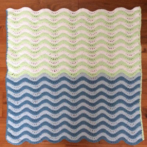 Free crochet pattern: Teeny Ripples preemie/stroller blanket in Lion Brand Feels Like Butta yarn by Underground Crafter | blanket laying flat