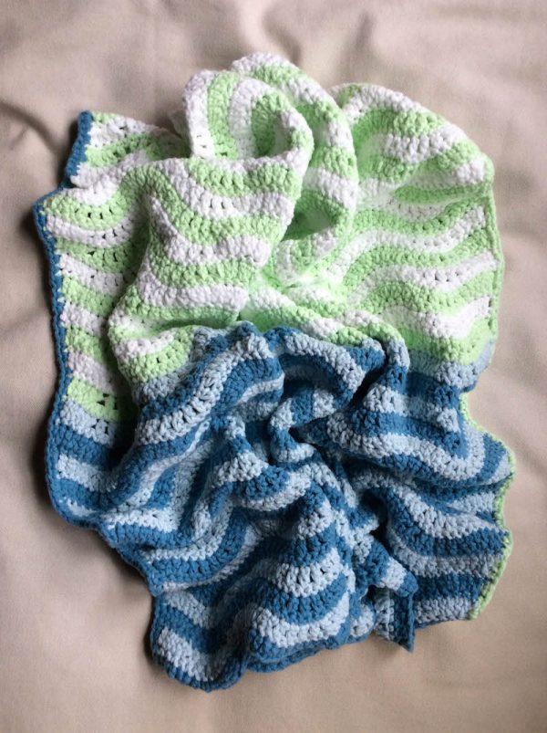 Free crochet pattern: Teeny Ripples preemie/stroller blanket in Lion Brand Feels Like Butta yarn by Underground Crafter | crumpled blanket on bed