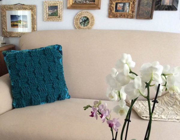 Twin Textures Pillow, free crochet pattern in Red Heart Sweet Home yarn by Underground Crafter | Basketweave side of pillow on couch