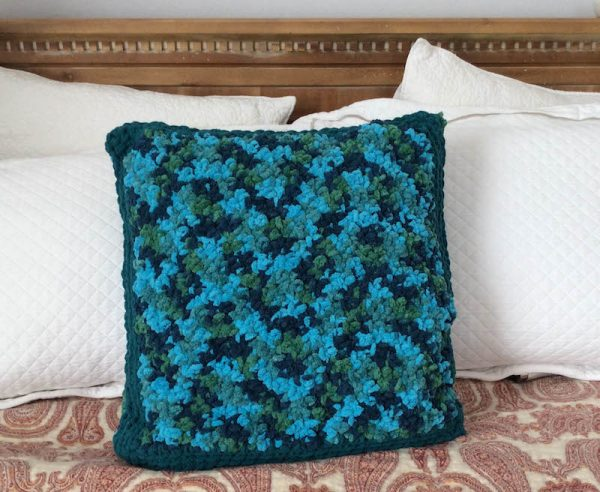 Twin Textures Pillow, free crochet pattern in Red Heart Sweet Home yarn by Underground Crafter | Pebble Stitch side of pillow on bed