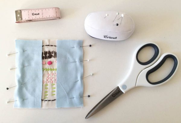 Boho Stitch Sampler Pillow with Cricut Maker Tutorial by Underground Crafter | Pinned front of pillow with pin cushion, scissors, and measuring tape
