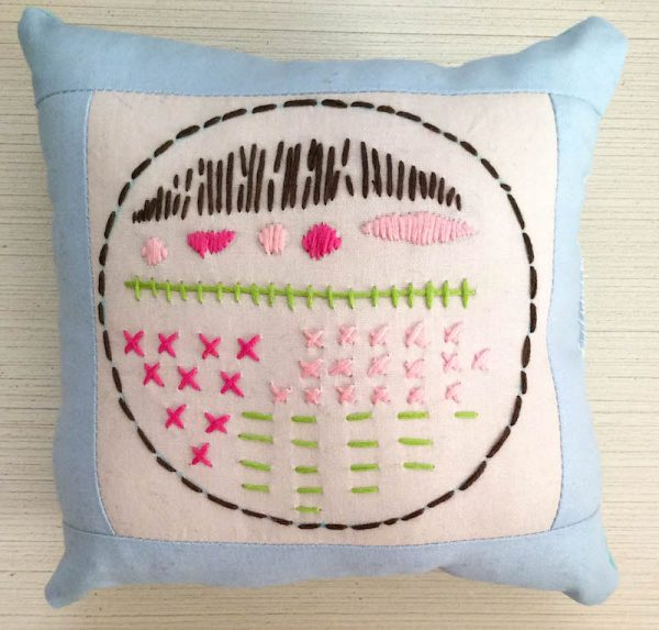 Boho Stitch Sampler Pillow with Cricut Maker Tutorial by Underground Crafter | Embroidery sampler pillow against wood background