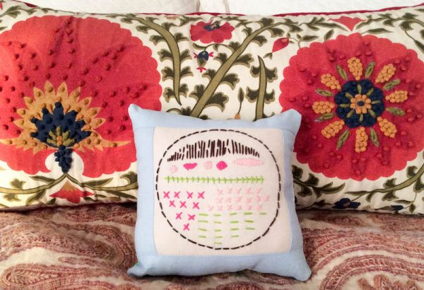 Boho Stitch Sampler Pillow with Cricut Maker Tutorial by Underground Crafter | Embroidery sampler pillow against bedspread with embroidered pillow