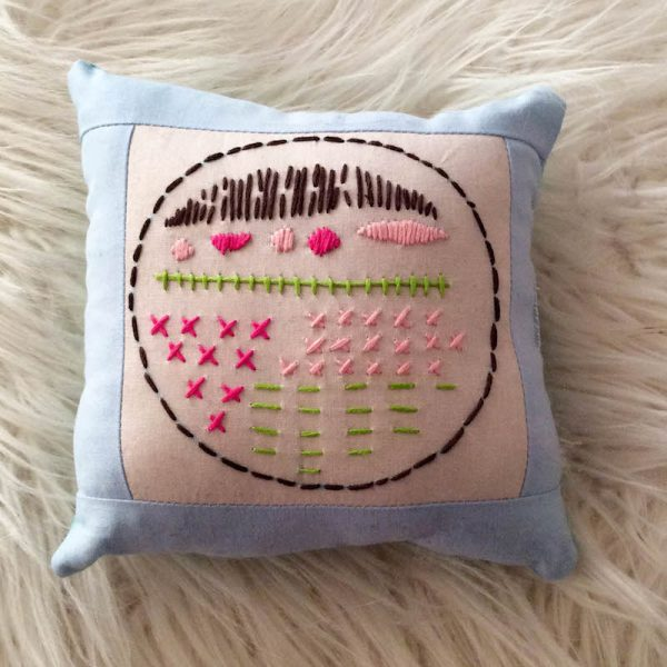 Boho Stitch Sampler Pillow with Cricut Maker Tutorial by Underground Crafter | Embroidery sampler pillow against faux fur background