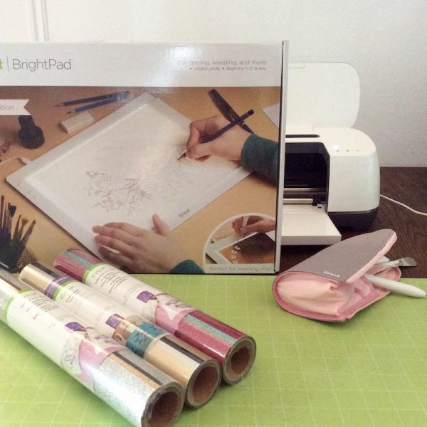 Cricut Basics: Get To Know the Cricut BrightPad with 9 BrightPad Projects via Underground Crafter | Cricut Maker with Cricut BrightPad in box, vinyl, cutting mat, and tools