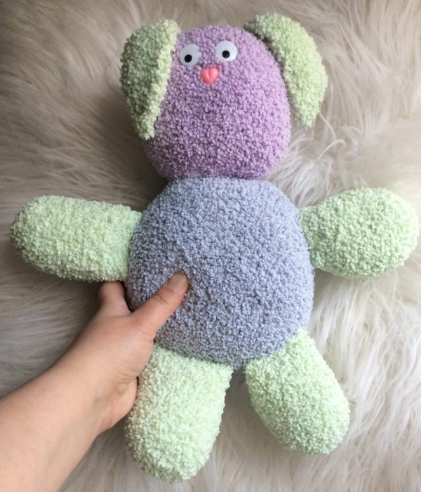 Bouncy Bouclé Bunny, free crochet pattern by Underground Crafter in Lion Brand Baby Soft Bouclé yarn, stuffed with Fairfield Poly-Fil Crafter's Choice Dry Polyester Packing Fiber Fill - bunny on faux fur background with hand for size reference