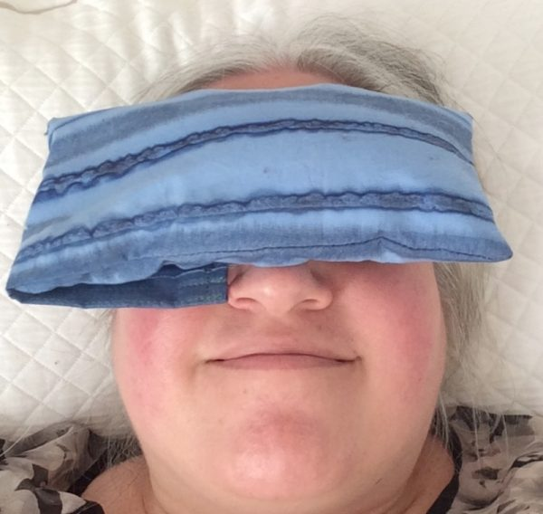 Weighted Flaxseed Eye Pillow with Case, free sewing tutorial by Underground Crafter - Marie smiling with eye pillow and resting